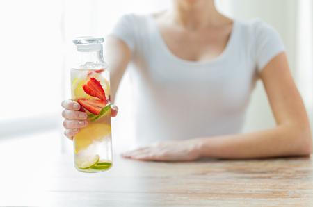 gesunde Ernährung, Getränke, Ernährung, Entgiftung und Konzept Menschen - in der Nähe der Frau mit Fruchtwasser in Glasflasche nach oben