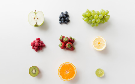 objects: diet, eco food, healthy eating and objects concept - ripe fruits and berries on white surface