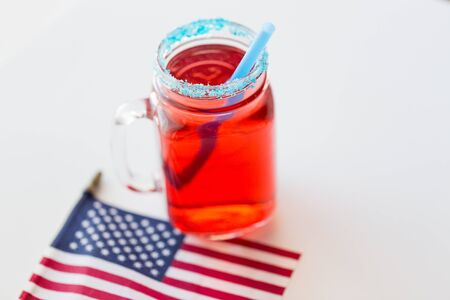 american independence day, celebration, patriotism and holidays concept - close up of juice glass and flag at 4th july party from top