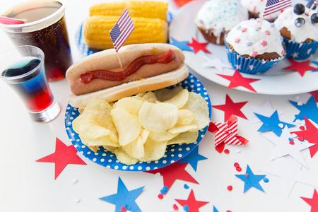 dog days: fiestas nacionales, celebración, comida y patriotismo concepto - cerca de perro caliente con el americano decoración bandera, papas fritas y bebidas el 4 de julio en la fiesta de Día de la Independencia Foto de archivo