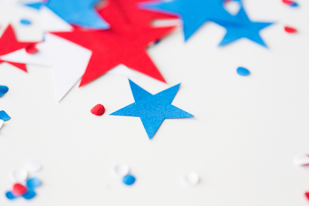 memorial: american independence day, celebration, patriotism and holidays concept - red and blue paper stars confetti on american independence day party