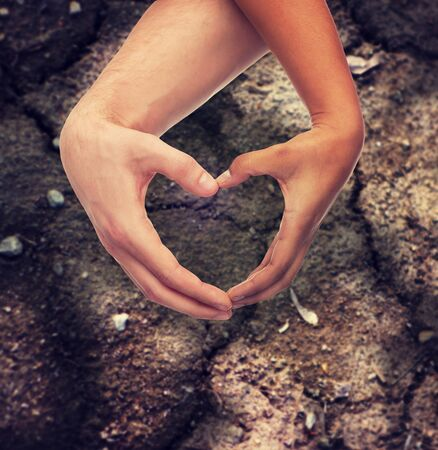 couples in love: love, care, hope and charity concept - closeup of woman and man hands showing heart shape over ground background