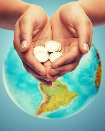 dinero, la gente, la economía, la caridad protección del medio ambiente y las finanzas concepto - cerca de las manos ahuecadas mujer monedas de euro y fondo azul