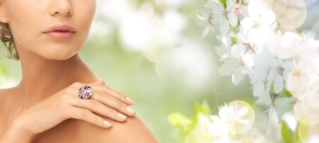 diamond rings: beauty, jewelry, people and accessories concept - close up of woman with cocktail ring on hand over summer garden and cherry blossom background
