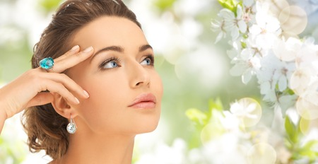 beauty, jewelry, people and accessories concept - close up of woman face with cocktail ring on hand and earrings over summer garden and cherry blossom background