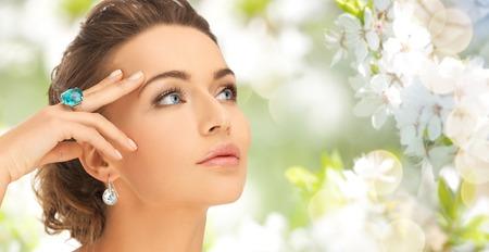 schoonheid, juwelen, mensen en accessoires concept - close-up van de vrouw geconfronteerd met een cocktail ring op de hand en oorbellen over de zomer tuin en achtergrond van de kersenbloesem