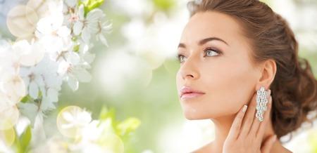 mensen, schoonheid, sieraden en accessoires concept - mooie vrouw met diamanten oorbellen over de zomer tuin en achtergrond van de kersenbloesem