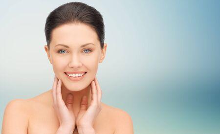 Beauté, personnes et concept de santé - belle jeune femme touchant son visage et son cou sur fond bleu Banque d'images