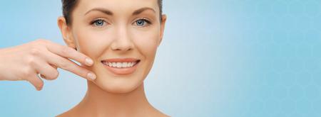 cuidado de la salud, las personas y el concepto de belleza - mujer hermosa que toca su piel de la cara sobre fondo azul