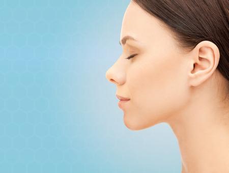 건강, 사람, 성형 수술 및 미용 개념 - 파란색 배경 위에 아름 다운 젊은 여자의 얼굴