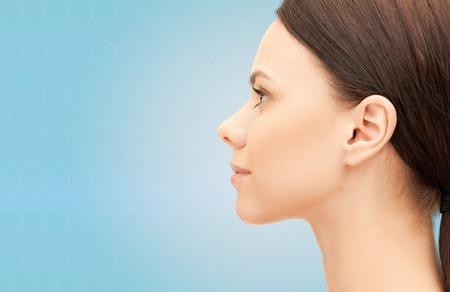 健康、人々、整形手術、美容コンセプト - 青い背景の上の美しい若い女性の顔