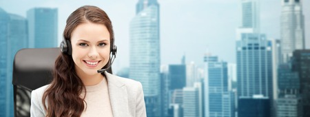 people, online service, communication and technology concept - smiling female helpline operator with headset over singapore city background