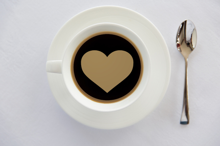 caffeine free: drinks, morning, love and valentines day concept - cup of black coffee with heart shape symbol on surface, spoon and saucer on table