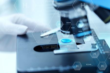la science, la chimie, la biologie, la médecine et les gens concept - gros plan de la main avec le scientifique échantillon d'essai sur la recherche en laboratoire clinique sur la formule chimique de l'hydrogène Banque d'images