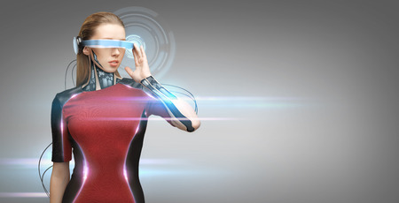 people, technology, future and progress - young woman with futuristic glasses and microchip implant or sensors over gray background with virtual projection and laser light Stock Photo