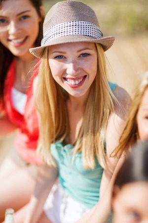 non alcoholic beer: summer holidays and vacation - girl with drink and friends on the beach Stock Photo
