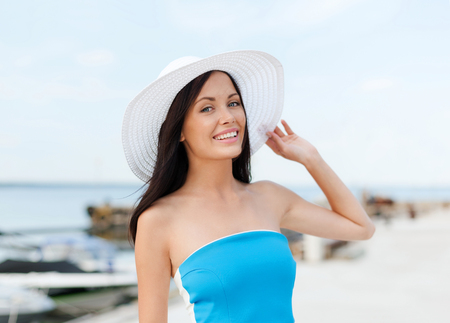 zomervakantie en vakantie concept - meisje in de hoed staat op het strand