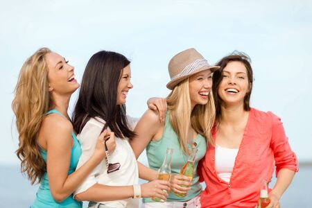 non alcoholic beer: summer holidays and vacation concept - smiling girls with drinks on the beach