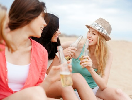 non alcoholic beer: summer holidays and vacation concept - girls with drinks on the beach