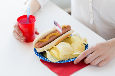 food state: independence day, celebration, patriotism and holidays concept - close up of woman hands eating hot dog with american flag decoration, potato chips and juice in cup on 4th july at home party