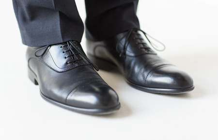 people, business, fashion and footwear concept - close up of man legs in elegant shoes with laces or lace boots Stock Photo