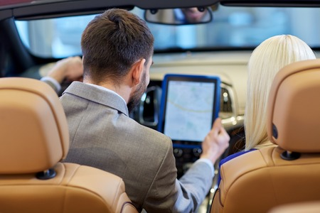back up: auto business, car sale, navigation and people concept - close up of couple sitting in cabriolet car with tablet pc computer at auto show or salon from back Stock Photo