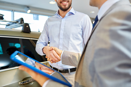 auto business, car sale, deal, gesture and people concept - close up of happy man and car dealer with tablet pc computer shaking hands in auto show or salon