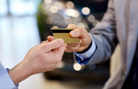 deal: auto business, sale and people concept - close up of customer hand giving credit card to car dealer in auto show or salon