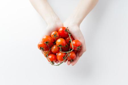 female hands: healthy eating, dieting, vegetarian food and people concept - close up of woman hands holding cherry tomatoes bunch at home