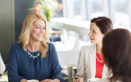 mujer tomando cafe: personas, la comunicaci�n y el estilo de vida concepto - mujeres felices beber caf� y hablando en el restaurante Foto de archivo