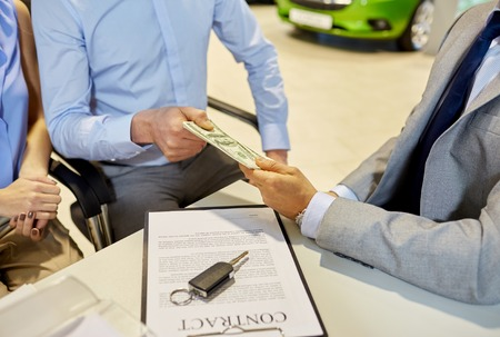 buying: auto business, sale and people concept - close up of customers giving money to dealer and buying car in auto show or salon