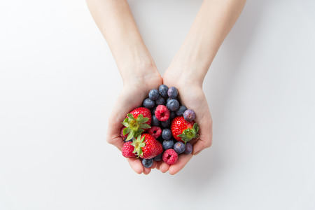 healthy eating, dieting, vegetarian food and people concept - close up of woman hands holding berries at home