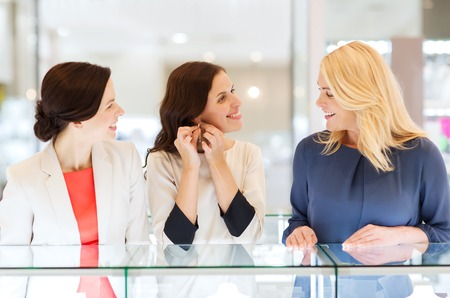 silver jewelry: sale, consumerism, shopping and people concept - happy happy women choosing and trying on earrings at jewelry store Stock Photo