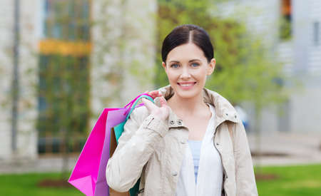consumerism: consumerism, leisure and people concept - smiling woman with shopping bags coming from sale in park Stock Photo