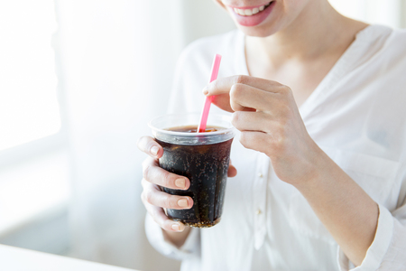 drinks, people and lifestyle concept - close up of happy woman drinking coca cola from plastic cup with straw at home