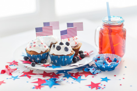 patriotism: celebration, patriotism and holidays concept - close up of glazed cupcakes decorated with american flags, juice glass or mason jar, popcorn and candies at 4th july party on independence day