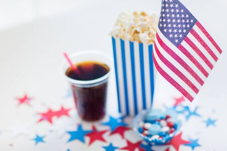 july 4th fourth: celebration, patriotism and holidays concept - close up of american flag, cup, popcorn and candies with stars confetti decoration at 4th july party on independence day