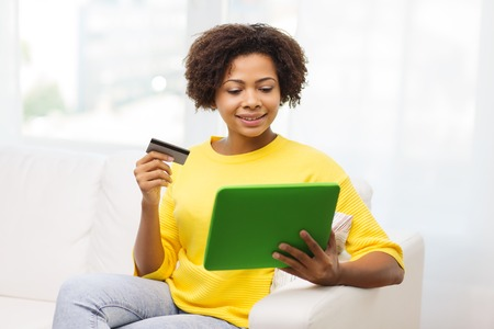 e money: people, internet bank, online shopping, technology and e-money concept - happy african american young woman sitting on sofa with tablet pc computer and credit card at home