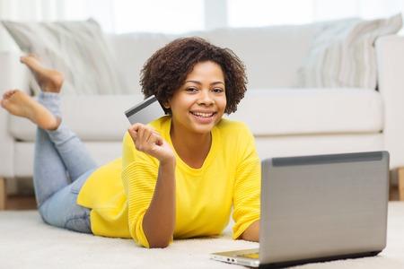 personas, banco por Internet, compras en línea, la tecnología y el concepto de dinero electrónico - feliz mujer joven afroamericana tirado en el suelo con el ordenador portátil y una tarjeta de crédito en casa