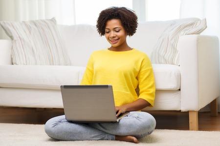 black girl: Mensch, Technik und Freizeit-Konzept - happy African American junge Frau sitzt auf dem Boden mit Laptop-Computer zu Hause