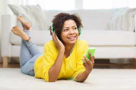 beautiful black woman: people, technology and leisure concept - happy african american young woman lying on floor with smartphone and headphones listening to music at home