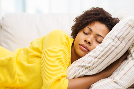 durmiendo: la gente, el descanso, la comodidad y el concepto de ocio - afroamericano mujer durmiendo en el sofá en casa Foto de archivo