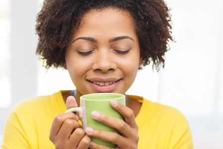 african coffee: people, drinks and leisure concept - happy african american woman drinking tea from cup or mug at home Stock Photo