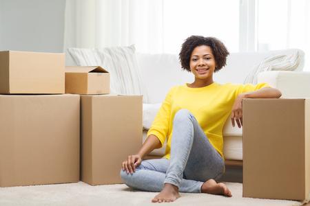 Mensen, het verplaatsen nieuwe plaats en reparatie concept - Gelukkig Afro-Amerikaanse jonge vrouw met vele kartonnen dozen zitten op de vloer thuis Stockfoto - 53856908