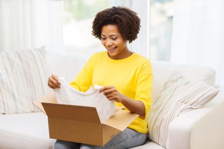 사람, 배달, 상거래, 운송 및 우편 서비스 개념 - 행복 한 아프리카 계 미국인 젊은 여자 골 판지 상자 또는 소포 집에서 옷을 복용