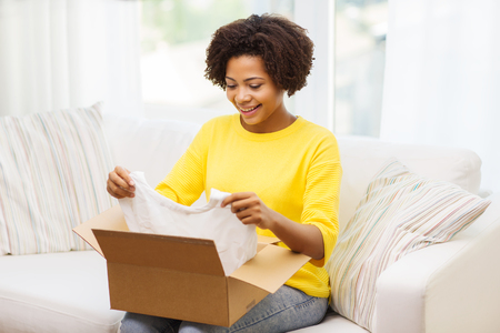 order delivery: people, delivery, commerce, shipping and postal service concept - happy african american young woman taking clothes out of cardboard box or parcel at home Stock Photo