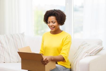 사람, 배달, 운송 및 우편 서비스 개념 - 행복 한 아프리카 계 미국인 젊은 여자 골 판지 상자 또는 소포 집에서 열기 스톡 콘텐츠