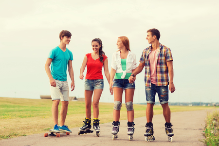 young boys: holidays, vacation, love and friendship concept - group of smiling teenagers with roller skates and skateboard riding outdoors