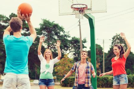 baloncesto chica: grupo de adolescentes sonrientes jugando al baloncesto al aire libre - las vacaciones de verano, días de fiesta, juegos y concepto de amistad