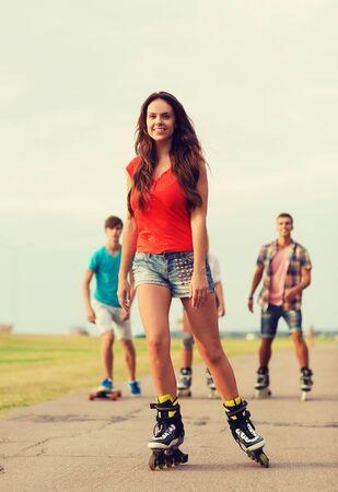 niño en patines: días de fiesta, vacaciones, el amor y el concepto de amistad - grupo de adolescentes sonrientes con patines y montar patineta al aire libre Foto de archivo